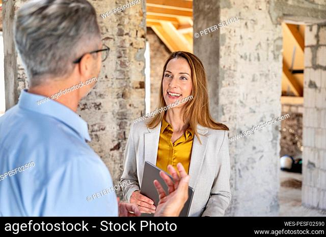 Engineer explaining to businesswoman while standing at construction site