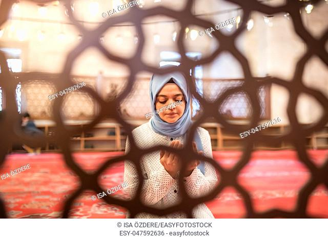 View through fence:Muslim woman in headscarf and hijab prays with her hands up in air in mosque. Religion praying concept