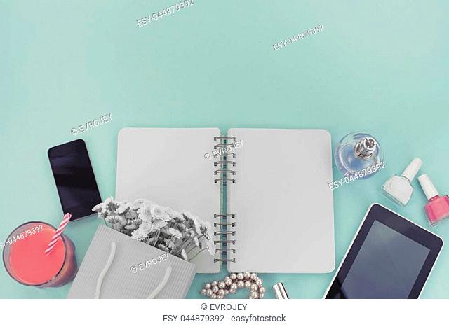 The opened notebook for records lies on the surface of the cocktail pink glass tube bouquet chrysanthemum perfume tablet box gift telephone
