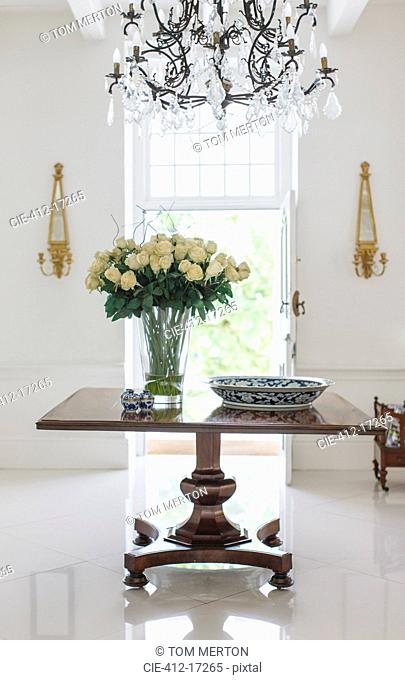 Chandelier over bouquet on table in luxury foyer