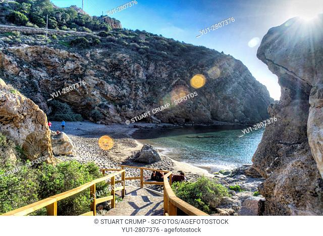 HDR image of sunlight with flare over Cala Cortina beach at Cartagena in Murcia Spain