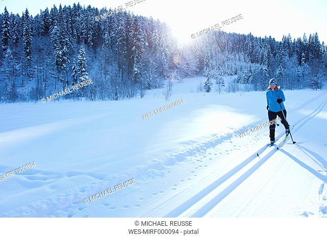 Germany, Bavaria, Isar Valley, Senior woman doing cross country skiing
