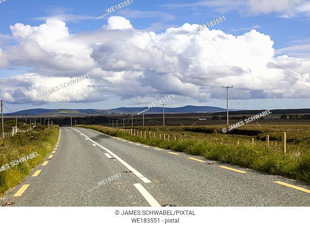 Looking down long paved road in rural northwestern Ireland