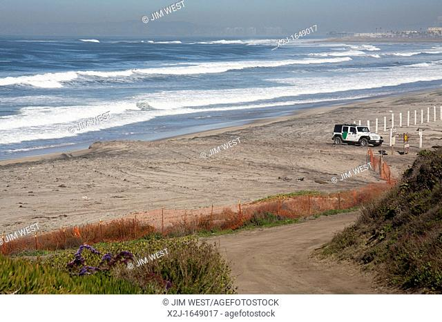 San Ysidro, California - A U S  Border Patrol Jeep guards the beach at the Pacific Ocean, just north of the border fence  The hotels of San Diego can be seen...