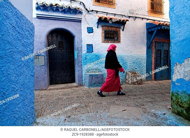 Woman walking on the blue streets of the medina, Chefchaouen, Rif region, Morocco