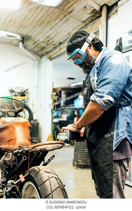 Mature man, working on motorcycle in garage