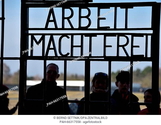 """Visitors walking through the gate with the words """"""""Arbeit macht frei"""""""" at the former Sachsenhausen concentration camp in Oranienburg, Germany, 1 March 2016"""