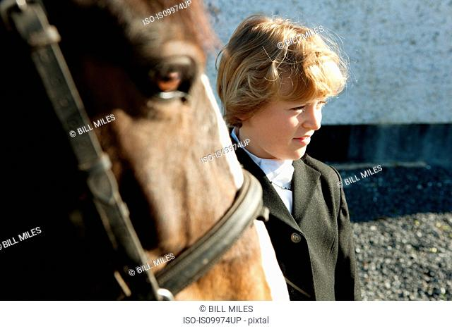 Boy standing with horse