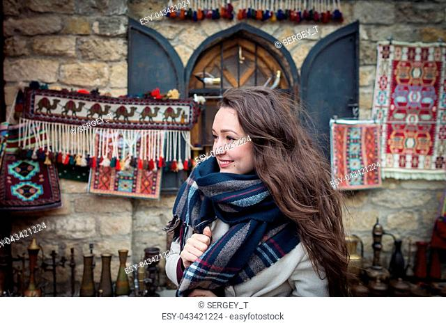 Young woman stands near a beautiful showcase on the eastern market. Curious traveler explores authentic oriental bazaar in Central Asia in winter season