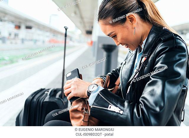 Woman sitting on train platform, looking through handbag, suitcase beside her, holding smartphone