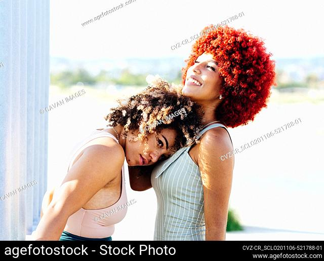 Two attractive latin girls with afro hair in an attitude of love