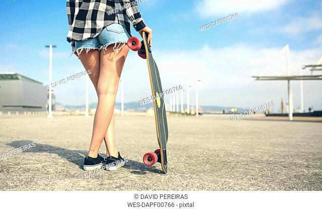 Back view of young woman with longboard in front of beach promenade, partial view
