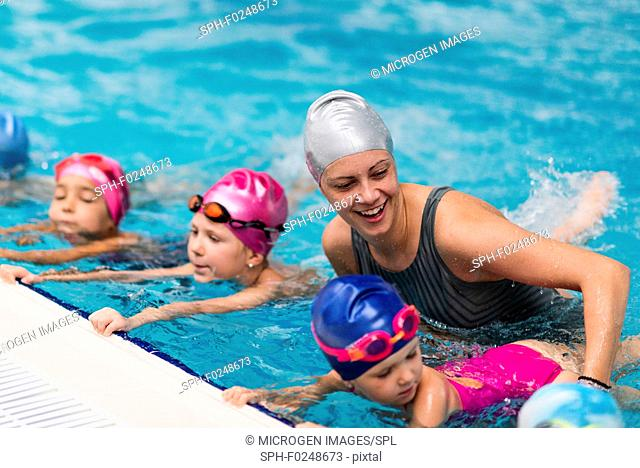 Swimming school. Swimming instructor with children