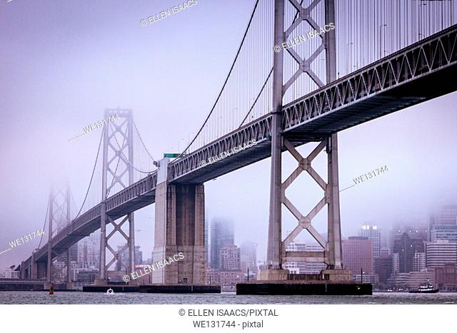 San Francisco Bay Bridge and the city from the water on a cold and foggy day