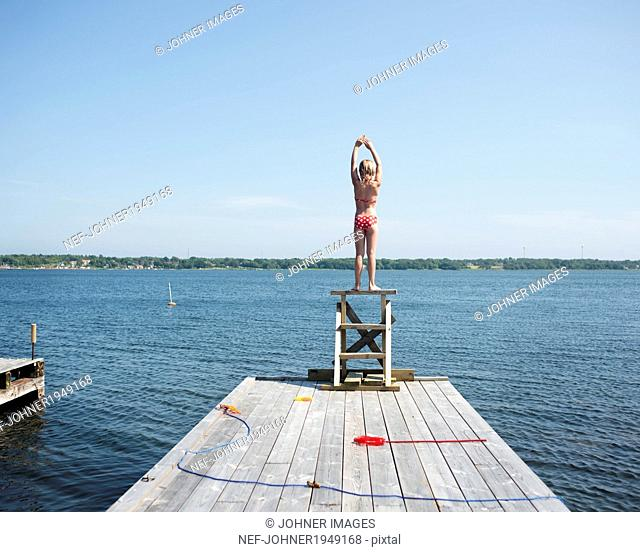 A girl diving from a jetty