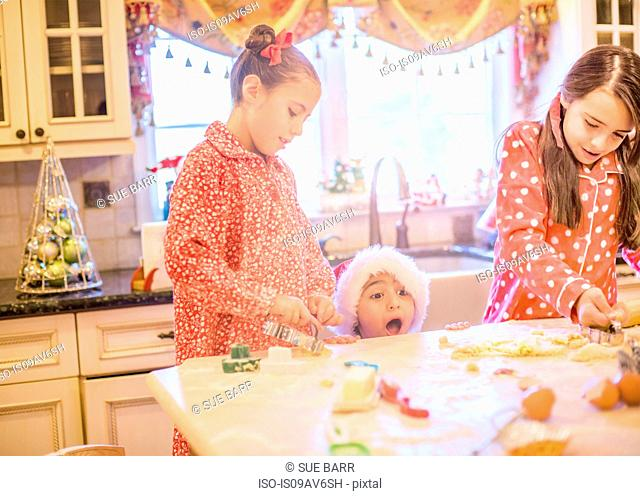 Boy in kitchen wearing santa hat making cookies with sisters peeking over kitchen counter open mouthed