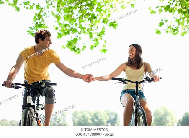 Couple riding bicycles and holding hands