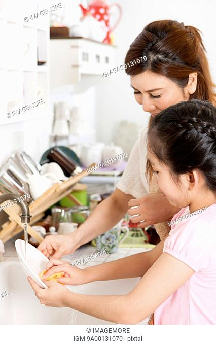 Mother teaching daughter to wash a plate