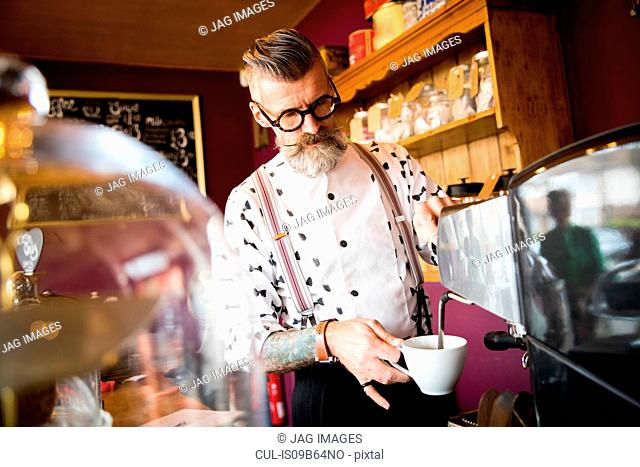 Quirky vintage senior man preparing coffee behind cafe counter