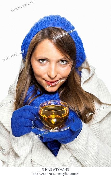 young woman with dark hair and blue wool hat drinking a cup of tea to wäremen is isolated on white background