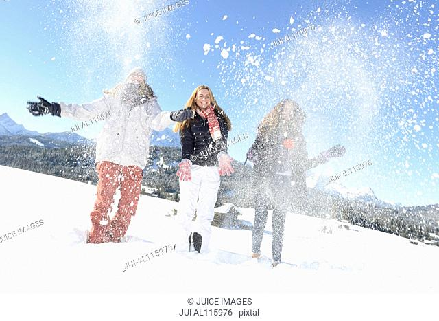 Young woman and teenage friends throwing snow on mountain