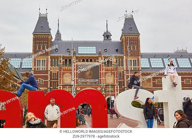 Tourists climbing on the I Amsterdam giant letters marketing slogan with Rijksmuseum behind, Museumplein (Museum Square), Amsterdam, Holland