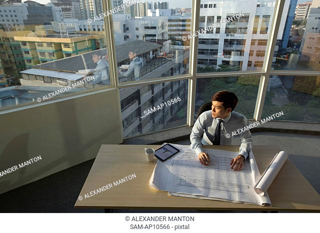 Singapore, Architect sitting in office looking out of window