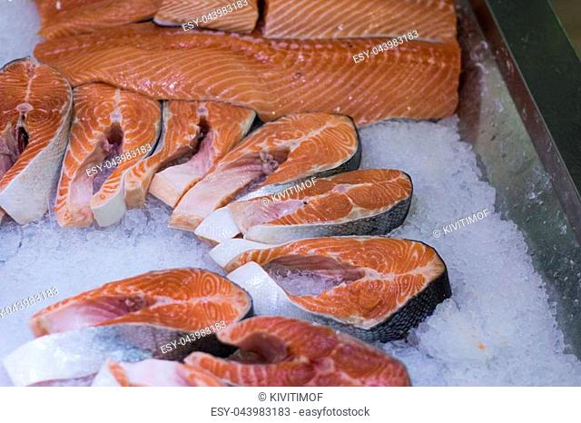 A lot of salmon steaks in the ice in the store