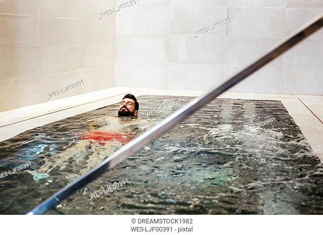 Man floating in a whirlpool in a spa