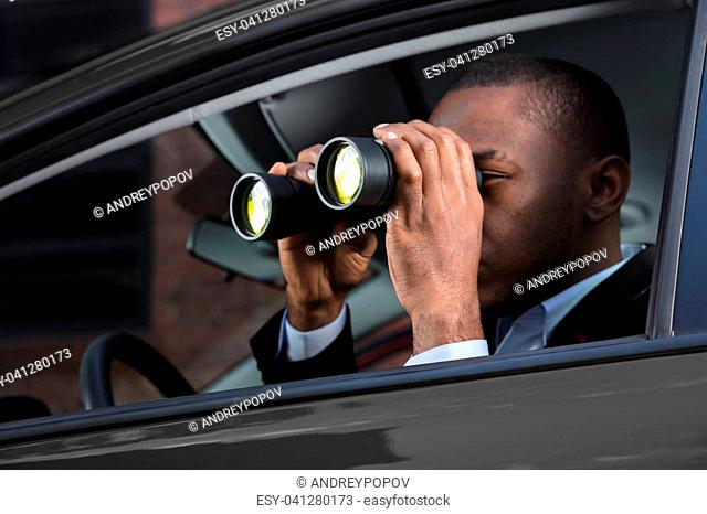 Close-up Of An African Man Sitting Inside Car Looking Through Binocular