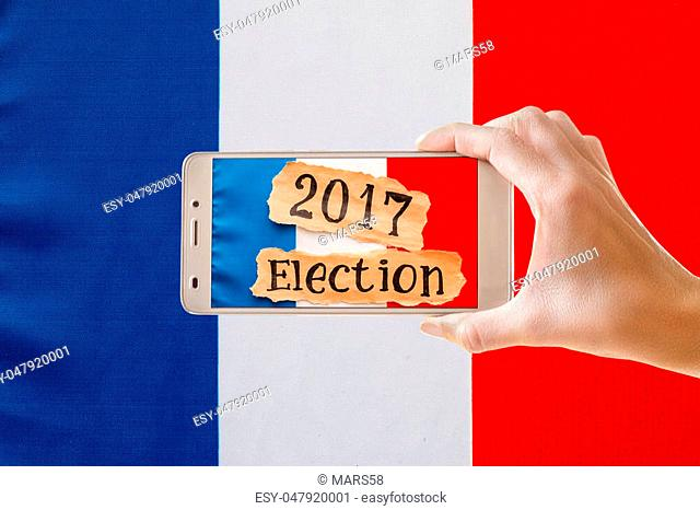 Elections in France. Female hand holding mobile smart phone with an inscription Election 2017