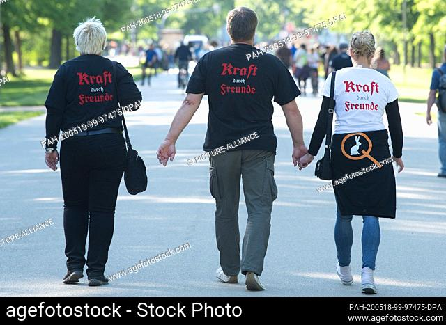 16 May 2020, Saxony, Dresden: Participants of a rally of supporters of conspiracy theories on the Corona crisis wear a T-shirt in the Great Garden with the...