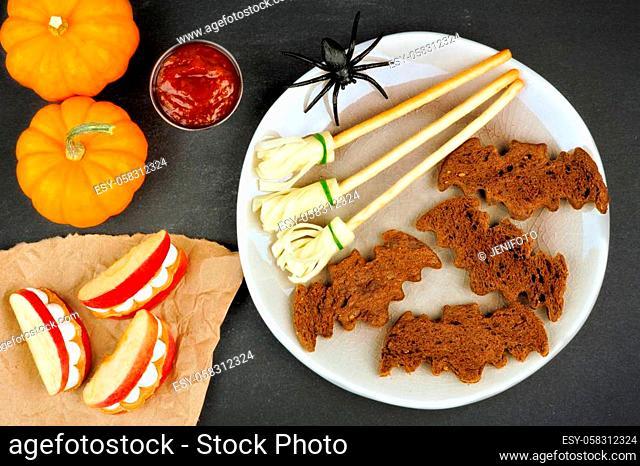 Halloween party food with bat breads, broomsticks and monster apple teeth, overhead scene on slate