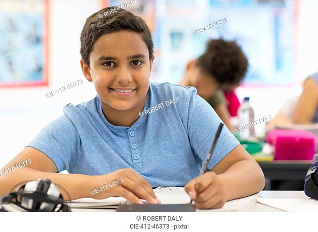 Portrait confident junior high school boy student doing homework in classroom