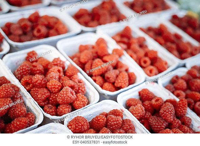 Assortment Of Fresh Yummy Organic Red Berries Raspberries At Produce Local Market In Trays, Containers