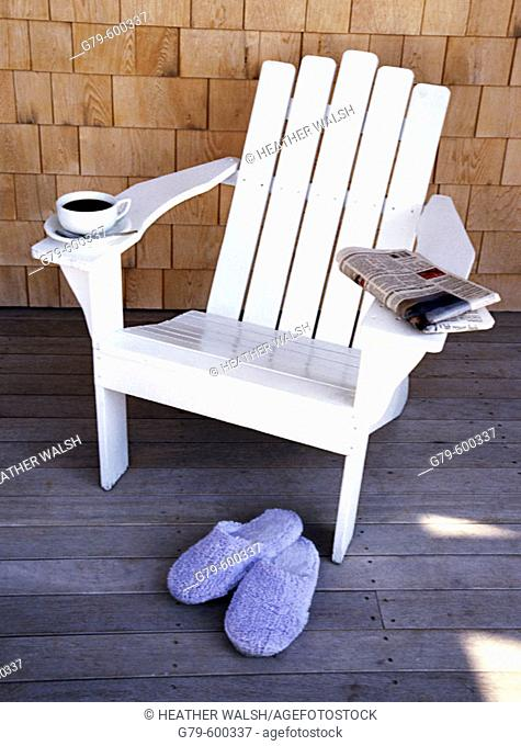 Still life with chair with morning newspaper, slipper and coffee