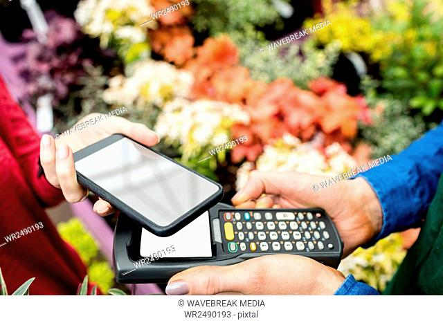 Hands making payment through smartphone
