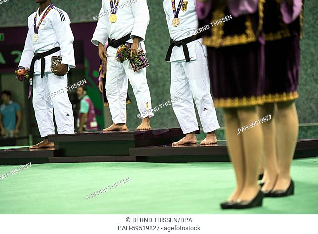 Germanys Sebastian Seidel (L) attemps with winner Kamal Khan-Magomedov (M, Russia) and second Loic Korval of France the medal ceremony after winning the bronze...