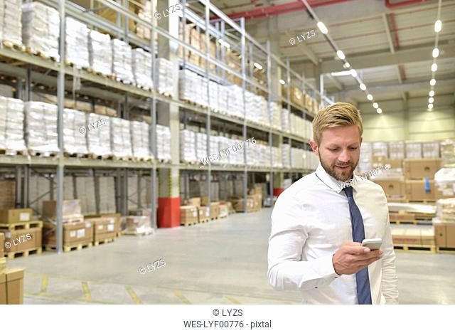 Smiling businessman looking at cell phone in warehouse