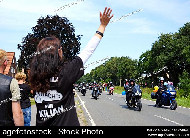 """24 July 2021, Lower Saxony, Rhauderfehn: A woman wearing a T-shirt with the inscription """"""""Krach für Kilian"""""""" waves to the motorcyclists riding past the house of..."""