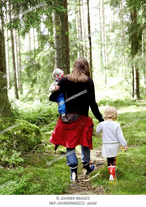 A woman with two children in the forest, Sweden