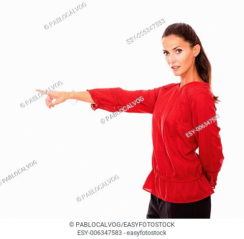 Portrait of attractive adult brunette pointing to her right while looking at you and standing on isolated white background - copyspace