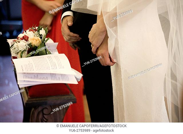 Hands of bride and groom, in church