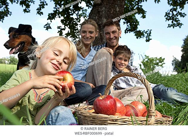 Germany, Bavaria, Altenthann,Girl with basket of apples, family with dog in background