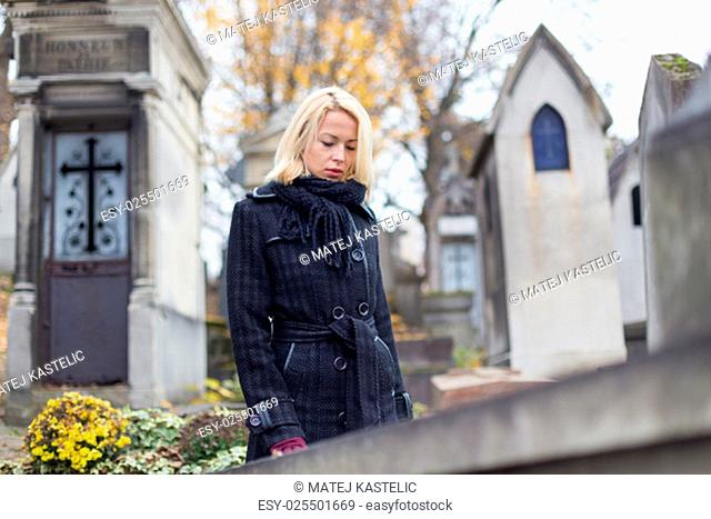 Solitary woman mourning by gravestone, remembering dead relatives in on Pere Lachaise cemetery in Paris, France