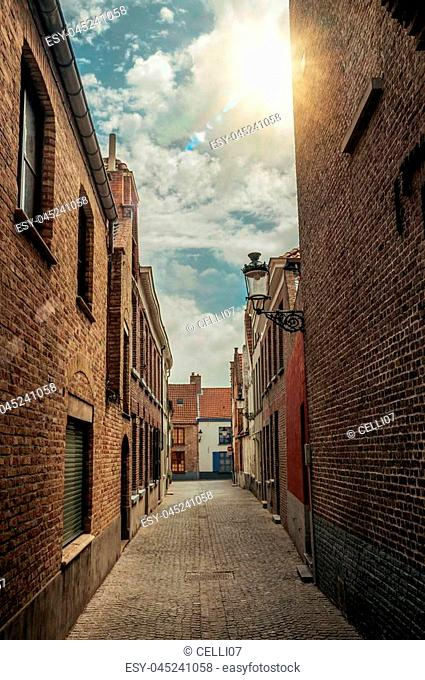 Narrow alley with brick walls and sunshine at City Center of Bruges. With many canals and old buildings, this graceful town is a World Heritage Site of Unesco