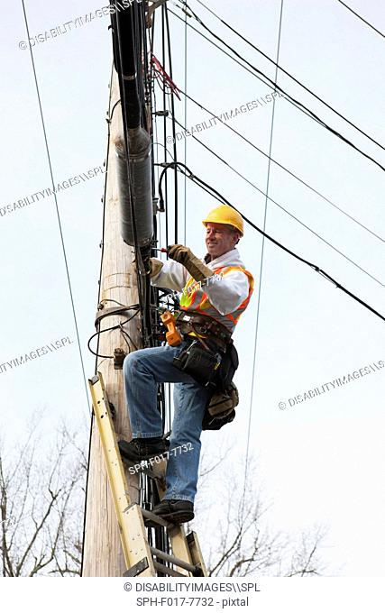 Communications worker attaching clamps to new cable bundle on power pole
