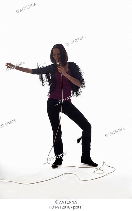 A female singer performing, studio shot, white background, back lit