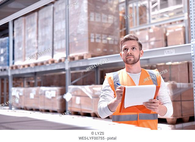 Man in factory hall wearing safety vest holding clipboard