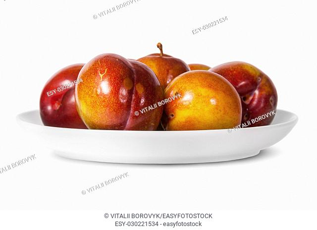 In front red and yellow plums on white plate isolated on white background